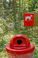 Dog waste receptacle and sign on a hiking trail on Bowen Island near Vancouver, British Columbia, Canada