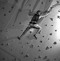 climber with prosthetic leg, climbing manufactured climbing wall in gym; determination; handicapped; sports, triumph, success, facing overcoming obstacles, black and white image; 4x5 original. Jason Hanford.
