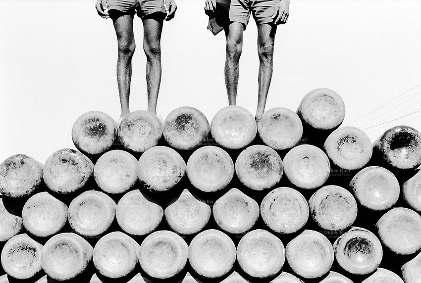 India. Province of Gujarat. Alang. Two men, both workers, stand up on a pile of oxygen tanks for welding. Alang, located in the Gulf of Khambhat, is a ships breaking place and is considered as the biggest scrapyard in the world. Ships recycling for its metals. Environmental issues. Hazardous waste. © 1992 Didier Ruef