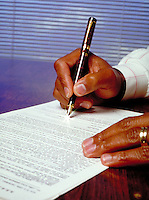 Close up of an African American man's hand signing a contract with a starburst at the tip of the pen. Black men, documents. R. Williams M.R. #R-8.