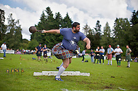 A competitor wearing a kilt throws a weight in an event at the Inveraray Highland Games, held at Inveraray Castle in Argyll.