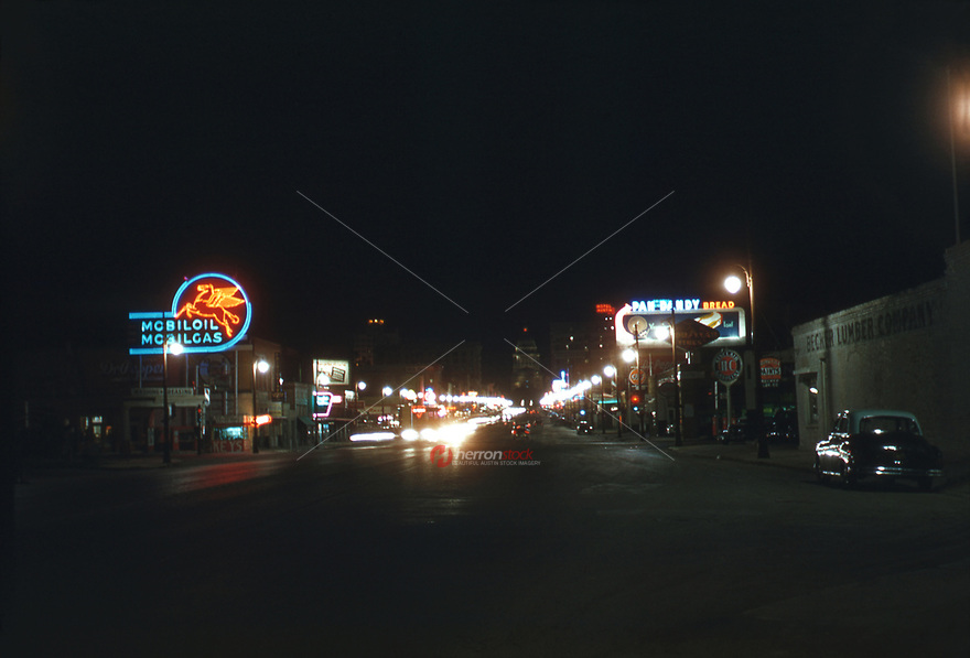 Unique nighttime view of retail shops and gas stations and the State Capitol as seen from north Congress Avenue looking south to downtown Austin, 1954.<br />