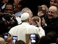 Papa Francesco bacia un bambino al suo arrivo all'udienza generale del mercoledi' in aula Paolo VI, Citta' del Vaticano, 7 dicembre 2016.<br /> Pope Francis waves faithful as he arrives to lead  his weekly general audience in Paul VI Hall at the Vatican on December 7, 2016. <br /> UPDATE IMAGES PRESS/Isabella Bonotto<br /> <br /> STRICTLY ONLY FOR EDITORIAL USE