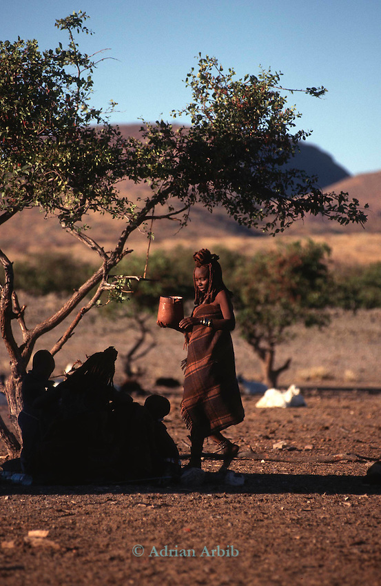 A Himba woman and container of milk  Northern Namibia.
