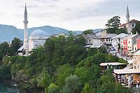Koski Mehmed Pasha's Pasa mosque along the Neretva river seen from the old bridge. The busy old market bazaar street Kujundziluk with lots of tourist craft and art shops and street merchants. Historic town of Mostar. Federation Bosne i Hercegovine. Bosnia Herzegovina, Europe.