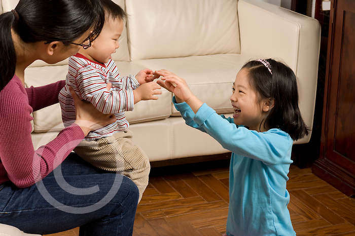 16 month old toddler boy held by mother anticipating tickle from 8 year old sister laughing horizontal