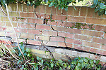 Impact damage to red brick garden wall caused by vehicle reversing, Suffolk, England, UK