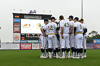 Michigan Wolverines team meeting including Eric Jacobson (12) and Carmen Benedetti (43) before the first game of a doubleheader against the Siena Saints on February 27, 2015 at Tradition Field in St. Lucie, Florida.  Michigan defeated Siena 6-2.  (Mike Janes/Four Seam Images)