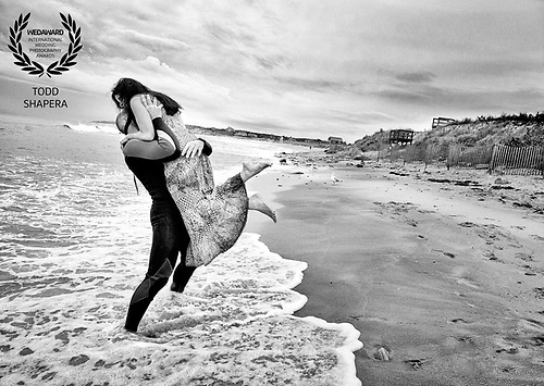 On their wedding morning, a couple hugs in the surf on a Montauk beach at sunrise.