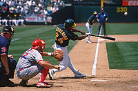 OAKLAND, CA - Rickey Henderson of the Oakland Athletics hits a home run during a game against the Texas Rangers at the Oakland Coliseum in Oakland, California on June 4, 1998. (Photo by Brad Mangin)