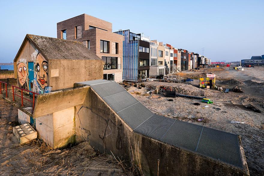 Nederland, Amsterdam, 14 feb 2015<br /> Bouwlokatie Zeeburgereiland. Op het voormalig terrein van de rioolwaterzuivering gaat een woonwijk verrijzen.  Een aantal kavels zijn zgn vrije kavels. Kopers van zo'n kavel mogen -binnen een aantal regels- zelf bepalen wat voor huis ze er neerzetten. De meeste bewoners kiezen voor zo veel mogelijk volume. De gevels zijn wel heel verschillend, de architectuur is niet echt heel afwijkend. Op het terrein staan nog wat restanten van vroeger, die blijven staan als markante herinneringen.<br /> Foto: (c) Michiel Wijnbergh