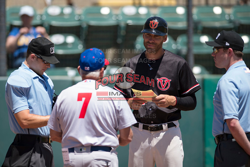 Visalia Rawhide manager Joe Mather (21) meets with Stockton Ports manager Rick Magnante (7) and umpires Andrew Barrett (left) and Darius Ghani (right) before a California League game at Visalia Recreation Ballpark on May 9, 2018 in Visalia, California. Stockton defeated Visalia 4-2. (Zachary Lucy/Four Seam Images)