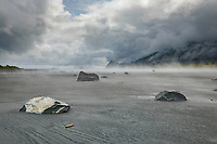 Summer landscape of sand, fog, rocks and shoreline at Bear Glacier Lagoon in Kenai Fjords National Park. Ailik Penninsula mountains in background.  Kenai Penninsula, Summer, Alaska   <br /> <br /> Photo by Jeff Schultz/  (C) 2019  ALL RIGHTS RESERVED