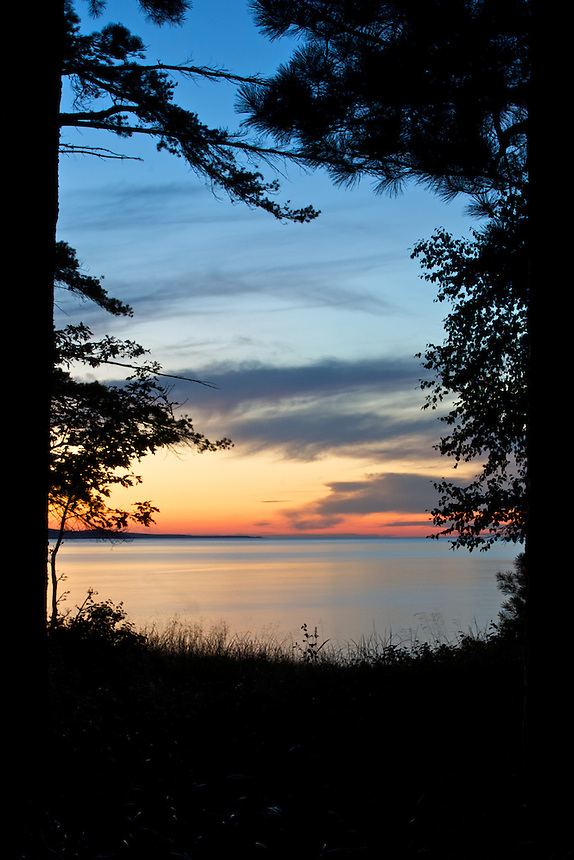 A colorful sunset over Lake Superior viewed through the trees.