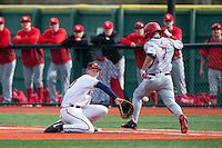 Pavin Smith (10) of the Virginia Cavaliers stretches for a low throw as Trey Stover (7) of the Hartford Hawks hustles down the first base line at The Ripken Experience on February 27, 2015 in Myrtle Beach, South Carolina.  The Cavaliers defeated the Hawks 5-1.  (Brian Westerholt/Four Seam Images)