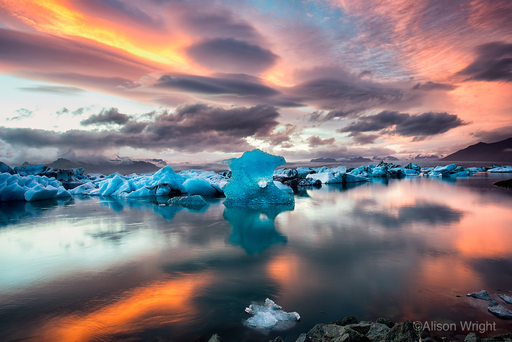 "Iceland, Jokulsarlon, Glacier lagoon. Skaftafell National Park.  Iceland, lying just below the Arctic Circle, is one of the fastest-warming places on the earth. According to the Daily Climate, the 300 some glaciers that cover 10 percent of the island are losing an average of 11 billion tons of ice a year. On this assignment I had just traveled Iceland and Greenland for the Hurtigruten cruise line, photographing the various incarnations of ice in all its magnificence. Once off the ship I drove across Iceland and one evening ended up in ""Iceberg Alley."" I watched as this iceberg flipped over and for the next three and a half hours photographed this ever-changing scene as the sun played out its captivating lightshow."