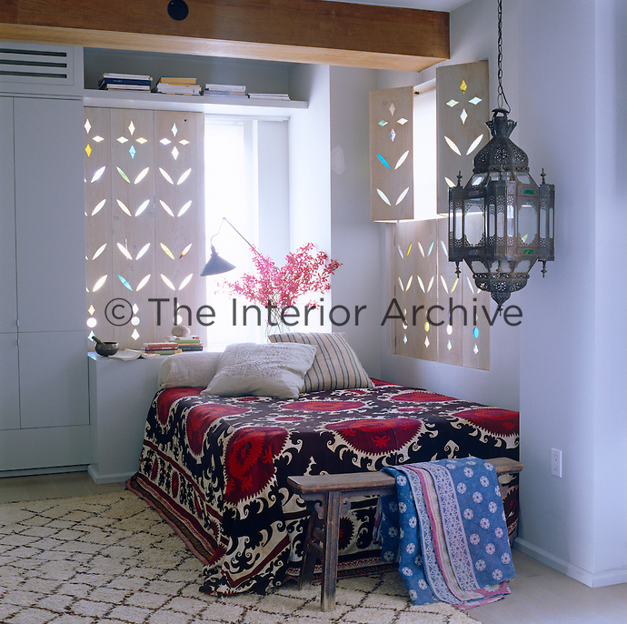 The bedroom has bespoke carved shutters that filter the sunlight through the windows on either side of the bed