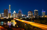 Austin skyline at twilight from across lady bird lake along congress and town lake with the iconic buildings like the Frost and Austonian with cars lights streaking by on the Congress bridge.