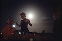 Sitting below the full moon on a night in the southern summer, a couple watches dancers at the Forró da Lua, or Forró of the Moon, on a ranch near São José de Mipibu, Brazil, Saturday, Jan. 14, 2006. (Kevin Moloney for the New York Times)