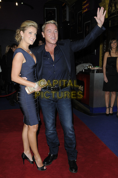 NIAMH O'BRIEN & MICHAEL FLATLEY .UK Premiere of 'Lord of the Dance 3D' at the Cineworld, Haymarket, London, England..March 10th 2011.full length navy black blue suit jacket jeans denim sleeveless dress married husband wife gold clutch bag hand palm waving arm.CAP/CAN.©Can Nguyen/Capital Pictures.