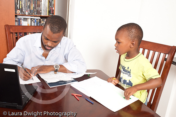 3 year old boy at home with his father modeling imitation father working on paperwork from job boy using crayon on pad horizontal