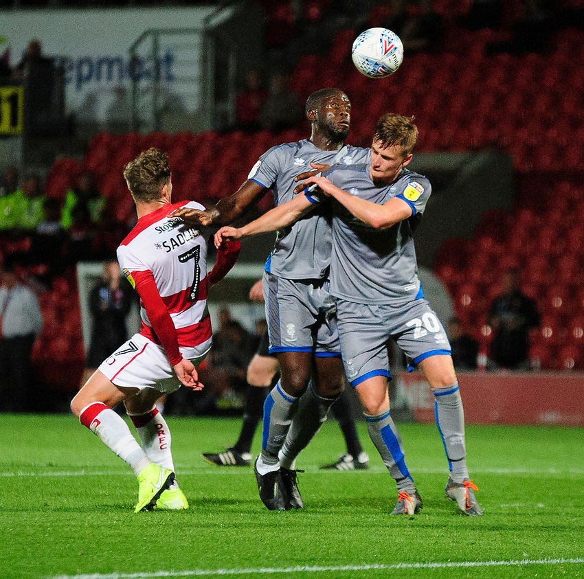 Lincoln City's John Akinde, left, and Callum Connolly battles with Doncaster Rovers' Kieran Sadlier<br /> <br /> Photographer Andrew Vaughan/CameraSport<br /> <br /> EFL Leasing.com Trophy - Northern Section - Group H - Doncaster Rovers v Lincoln City - Tuesday 3rd September 2019 - Keepmoat Stadium - Doncaster<br />  <br /> World Copyright © 2018 CameraSport. All rights reserved. 43 Linden Ave. Countesthorpe. Leicester. England. LE8 5PG - Tel: +44 (0) 116 277 4147 - admin@camerasport.com - www.camerasport.com