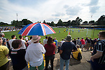 St Albans 0 Watford 5, 26/07/2014. Clarence Park, Pre Season Friendly. Pre Season friendly between St Albans City and Watford from Clarence Park Stadium. A fan uses an umbrella and a sun screen. Watford won the game 5-0. Photo by Simon Gill.