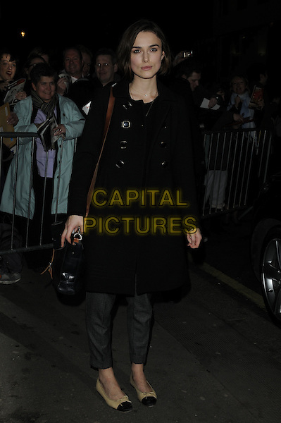 "KEIRA KNIGHTLEY.Departed after an evening performance of ""The Children's Hour"", The Comedy Theatre, London, England, UK,.3rd February 2011..full length brown flats pumps shoes beige two tone grey gray trousers strap bag purse black coat .CAP/CAN.©Can Nguyen/Capital Pictures."