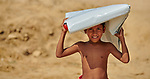 A Rohingya boy carries a tarp that he received from Christian Aid in the Jamtoli Refugee Camp near Cox's Bazar, Bangladesh. Christian Aid is a member of the ACT Alliance.<br /> <br /> More than 600,000 Rohingya have fled government-sanctioned violence in Myanmar for safety in Bangladesh.