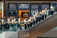 Employees of the Marina Bay Sands ride an escalator in a shopping mall during their lunch break.