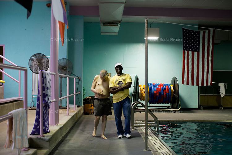 Caretaker Jean Robert Helas walks with Fernald Developmental Center resident Randy Russo as he waits for his turn to get in the pool at the Fernald Center Aquatics pool in the Green Building at Fernald in Waltham, Mass., USA. The twins Ronnie and Randy Russo go to the pool twice a week and, with help from Hebert, walk around the pool with light water weights as a way to get exercise and maintain limb strength.  Hebert was an employee at Fernald, but now volunteers as a swim tutor with the twins twice a week.