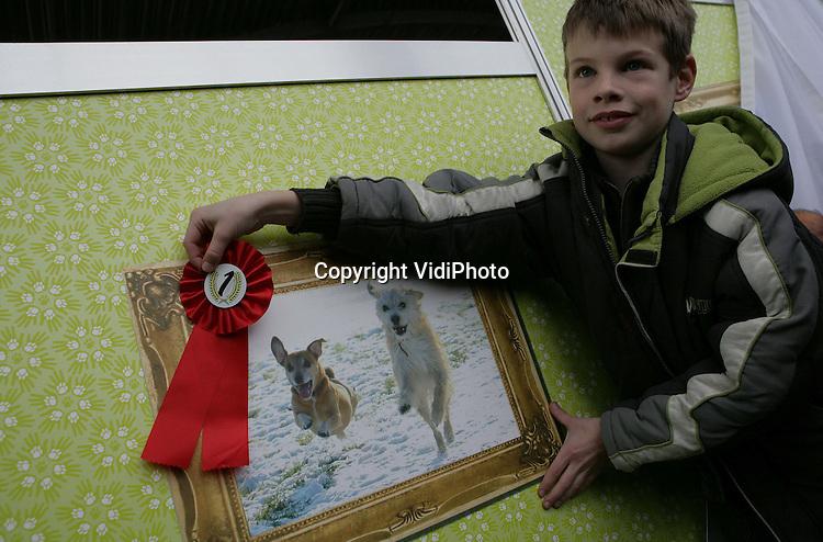 Foto: VidiPhoto..RHENEN - Met twee rennende honden in de sneeuw  is de negenjarige Etienne Rutten uit Wychen winnaar geworden van de jaarlijkse fotowedstrijd van Kids for Animals, de jeugdclub van de Dierenbescherming. In Ouwehands Dierenpark in Rhenen ontving Etienne zaterdag uit handen van dierenfotograaf Rob Doolaard de hoofdprijs: een jaarabonnement voor het dierenpark. Meer dan 3000 foto's werden er dit jaar ingestuurd voor de fotowedstrijd. Ieder jaar organiseert Kids for Animals de fotowedstrijd. Diervriendelijk fotograferen staat centraal.
