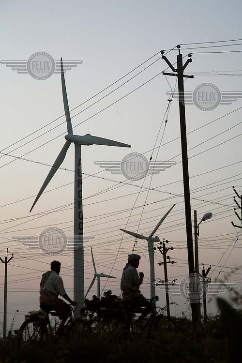 Men ride their bicycles past wind turbines and power lines at Muppandal wind farm. Muppandal is one of the largest wind farms in Asia.