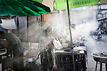 KADEEJEEN, BANGKOK, THAILAND, DECEMBER 2012:..Stret food vendor in the small street of Kadeejeen neighbourhood, Street food are like restaurant for local people, they go there to eat everyday and the food is amazing and very cheap, Dec 2012...The Kadeejeen neighbourhood comprises six communities  Wat Kalaya, Kudeejeen, Wat Prayurawong, Wat Bupparaam, Kudee Khao and Roang Kraam...Ever since the Thonburi era (in the 17th Century), these historic neighbourhoods have maintained the diverse cultural heritage of three religions and four beliefs (Theravada Buddhism, Mahayana Buddhism, Christianity and Muslim) while coexisting in peaceful harmony...The neighbourhood is still characterised by Bangkok's traditional urbanism which is that of a fine-grained, religious establishment-centred urban structure with close-knit social cohesion. ©Giulio Di Sturco/Reportage by Getty Images.