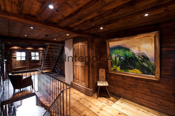 One wall of the first floor landing displays a contemporary landscape beside a traditional Alpine chair