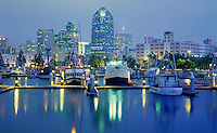 San Diego cityscape at dusk showing boats and harbor in foreground. San Diego California USA.