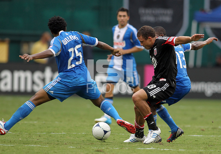 WASHINGTON, D.C. - AUGUST 19, 2012:  Nick DeLeon (18) of DC United gets the ball from Michael Lahoud (13) and Sheanon Williams (25) of the Philadelphia Union during an MLS match at RFK Stadium, in Washington DC, on August 19. The game ended in a 1-1 tie.