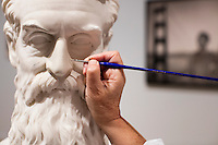 """Conservator Rika Smith McNally works on a replacement nose for a bust of abolitionist John Brown in the Tisch Family Gallery at the Tufts University Art Gallery at Tufts University in Medford, Massachusetts, on Thurs., Oct. 6, 2016. The bust was sculpted by Edward Augustus Brackett and had been improperly stored for decades with a broken nose and eyebrow. The conservators, from Rika Smith McNally and Associates, found a plaster cast made from the original at the Boston Athenæum and had a 3D modeler image the broken section of the original and the cast. They then used 3D printing technology to use to create a plaster nose replacement that would fit perfectly on the broken marble bust. They then used gouache paint to match the replacement pieces to the original marble.  The bust is part of an exhibition at the gallery entitled """"Mortal Things: Portraits Look Back and Forth."""""""