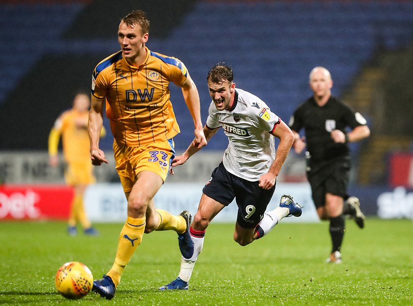 Bolton Wanderers' Christian Doidge chasing down Wigan Athletic's Dan Burn<br /> <br /> Photographer Andrew Kearns/CameraSport<br /> <br /> The EFL Sky Bet Championship - Bolton Wanderers v Wigan Athletic - Saturday 1st December 2018 - University of Bolton Stadium - Bolton<br /> <br /> World Copyright © 2018 CameraSport. All rights reserved. 43 Linden Ave. Countesthorpe. Leicester. England. LE8 5PG - Tel: +44 (0) 116 277 4147 - admin@camerasport.com - www.camerasport.com