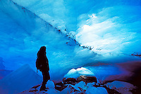 A hiker explores an ice cave at the terminus of the Nugget Creek Glacier, Juneau, Alaska in Tongass National Forest. (Southeast Alaska). Extreme caution is urged when exploring glaciers; they are extremely unstable. Juneau Alaska, Nugget Creek Glacier, He
