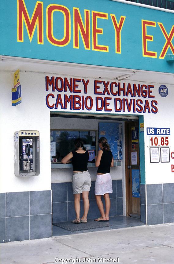 Two young women tourists exhanging money at a casa de cambio in Puerto Morelos, Quintana Roo, Mexico
