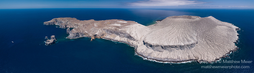 San Benedicto Island, Revillagigedos Islands, Mexico;  a panoramic aerial view of the cinder cone created in the 1952 volcanic eruption and the entirety of San Benedicto Island, as viewed from the windward side, with afternoon clouds overhead