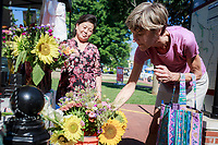 NWA Democrat-Gazette/CHARLIE KAIJO Mai Lee of Decatur looks on as Lisa Jackson of Bentonville looks at flowers at her booth during the farmer's market, Saturday, July 7, 2018 at the Square in Bentonville. <br /><br />Area Farmers Markets are participating in a farmers market trail where patrons have passports that are stamped when they visit pariticipating markets. The event takes place through July and is an attempt to celebrate the diversity within the region&Otilde;s markets.
