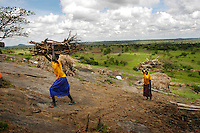 A northern Ugandan resident carries wood to their make-shift home on a hill in one of the many rural camps for internally displaced people spread across the northern region and filled with people  who fled attacks by the Lords Resistance Army. By 2004, the conflict had displaced two million people.