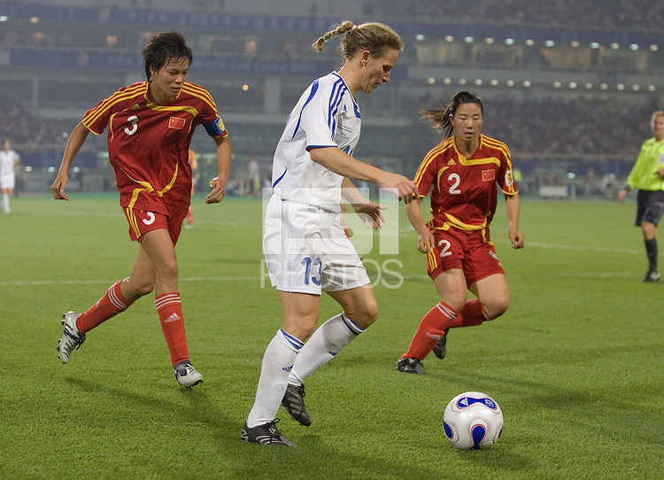World Stars Kristine Lilly dribbles the ball as China's Jie Li and Xiaomei Jin close in. The FIFA Women's World Stars played an exhibition match against China at the Wuhan Sports Center Stadium as part of the Women's World Cup Draw on April 21, 2007.