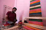 A Palestinian man, works on wood to make furniture at A workshop, in Gaza City, on June 20, 2019. Meqdad works with used wood boards and pieces to make artistic and creative furniture. Photo by Mahmoud Ajjour