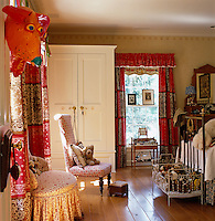 This girl's bedroom has an old-fashioned feel with a wrought-iron bed, checked curtains and a toy cot full of soft toys