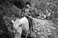 Peruvian boy takes the easier way along the Inca Trail, heading down, instead of up, on horseback. Good idea.