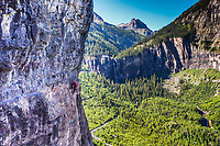 A climber traverses the Ferrata Route high above Telluride, Colorado as Bridal Veil Falls, Colorado's highest free falling waterfall at 365 feet, flows in the background.
