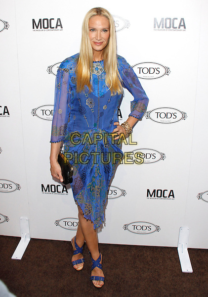KELLY LYNCH.The Diego Della Valle Cocktail Celebration Honoring Tod's Beverly Hills Boutique And MOCA's New Director Jerry Deitch at Tod's Boutique in Beverly full length blue purple dress print gold patterned open toe sandals bracelet black clutch bag sheer sleeves beaded hand on hip  .CAP/RKE/DVS.©DVS/RockinExposures/Capital Pictures.